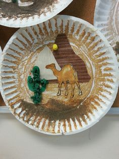 Desert craft: brown chalk on a paper plate, brown wallpapers cut into valleys, cactus cutouts with balled up tissue paper, camel printouts painted with orange and brown paint, sand glued to the bottom of the plate.