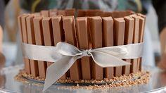 Receita com instruções em vídeo: Que tal dar de presente para quem você ama essa linda e deliciosa torta kitkat?  Ingredientes: 600g de kitkat, 1 lata de creme de leite, 450g de chocolate meio amargo derretido, 1 envelope de gelatina incolor sem sabor, 300g de creme de leite fresco, 4 colheres de sopa de açúcar, 100g de raspas de chocolate preto e branco para decorar