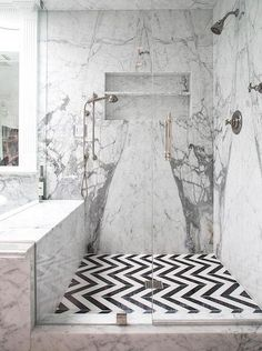 An large glass door entryway enhances the black and white, mixed pattern appeal . An large glass door entryway enhances the black and white, mixed pattern appeal of this shower enclosure. Chevron Bathroom, Black Marble Bathroom, Chevron Tile, Chevron Floor, Stone Bathroom, Black Chevron, Black Bathrooms, Tiny Bathrooms, Glass Bathroom