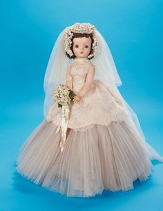 "Extremely Rare Cissy as ""Lucy Bride"" in Pale Rose by Alexander,1956 20"" (51 cm.) Hard plastic socket head,torso and legs with jointing at hips and knees,rigid vinyl arms with shoulder and elbow jointing,dark blue sleep eyes,lashes,closed mouth with reddish/coral lips,brunette curled hair. She is wearing a wedding gown with fitted separate bodice of white lace over rose silk underblouse,with long fitted sleeves and collar,matching overskirt that attaches to the bodice in the back (and with zipper"