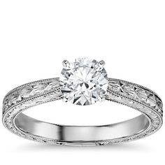 Exquisitely hand-engraved, this engagement ring features an intricate motif to showcase your center diamond in classic 14k white gold.