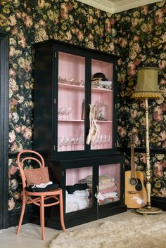 The light pink and black contrast perfectly in this room, and the curiosity cupboard looks great alongside this bold wallpaper!