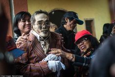 Relatives carefully dress a dead man in fresh clothes before reburying him on…