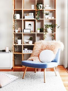 Blue slipper chair with faux fur throw and a tall Bookshelf behind // vignette