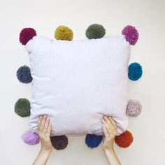 Add giant pom-poms to a plain cushion to add texture and colour to any sofa