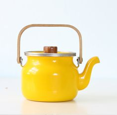 A bright yellow, a modern shape, the bentwood handle...its retro style at its finest. The enamel has a beautiful shine, and there is very little rusting. Even the inside is fairly clean, with just a little bit of staining near the spout. The wood also shows some wear and fading, both on the handle and on the knob. Add it to a room and youll have that cool retro look instantly! Size: 8 wide, 5 deep, 8 tall (with handle up) **glass ball and dried flower stems not included **convo...