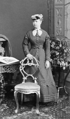 "This photo of Marie Alexandrovna is a superb example of late 1860s dress with the cone crinoline (probably a version called a ""crinolette"") and natural waistline. Her skirt flares out as a cone until almost the end where it hangs vertically in crinolette style. Her jacket bodice appears to have pockets below the waist band. Her jacket bodice appears to reach two-thirds of the way to the hem of her skirt"