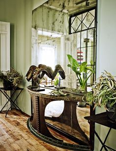 Greenery in entryway with foggy mirror and sculpture