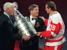 Gordie Howe, left and Ted Lindsay, present the Stanley Cup to Steve Yzerman during the pregame ceremony.