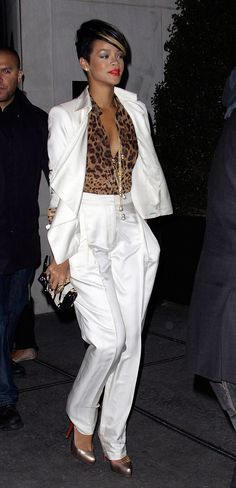 Rihanna debuted a white-hot Derek Lam pantsuit with a dash of growl power, via her sheer leopard blouse, in 2009. The singer accessorized her NYC street style with an array of gold jewels, a Jimmy Choo clutch, and metallic platform pumps.