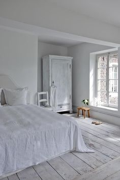 white bedroom full of light.  Needs a little color, but I like the floor