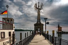 https://flic.kr/p/H9vnQy | Rotating Imperia | Imperia is a statue created by German sculptor Peter Lenk in 1993. Situated at the entrance of the harbour of Konstanz, Germany, it rotates slowly around its axis. The two men sitting on her hands represent Pope Martin V and Emperor Sigismund who played a role during the Council of Konstanz (1414-1418). The statue refers to a short story by Balzac criticizing Catholic morals of that time. (Source: Wikipedia). As usual, I did not carry my tripod…