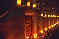 The adobe walls and wooden gates of Canyon Road in Santa Fe, New Mexico, are aglow with faralitos, small candles in  paper bags, on Christmas Eve. #newmexico #holidays #christmas