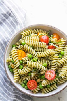 Quick and easy summer pesto pasta salad! with fresh basil pesto, spiral pasta, pine nuts, olives, peas, and cherry tomatoes. Takes less than 30 minutes to make! Perfect for a potluck! On SimplyRecipes.com