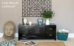 Low black #cabinet with #buddha head and window panel & orchid #accessories