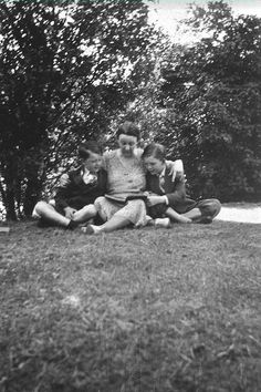 Marguerite deAngeli on Lawn with Sons Reading a Book
