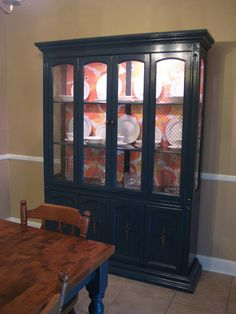 This is a great makeover idea for my tired old china cabinet. Love the printed background.