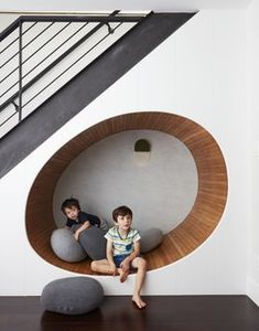 "Dark Hardwood Floor The space below the stairs was turned into a cheerful play area for the two boys. ""We built an egg shaped 'nook' underneath the staircase, and filled it with soft 'pebble' pillows,"" adds Tang."