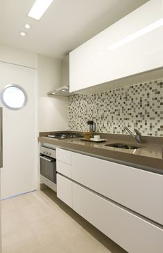 O projeto da cozinha segue um estilo minimalista, que prioriza as linhas retas. As gavetas e portas dos armários ficam praticamente invisíveis no móvel, o que é uma solução ideal para ambientes integrados com living. A iluminação foi pensada para ser funcional e, ao mesmo tempo, confortável.#lilianazenaro #lilianazenarointeriores#decor #decoracao #reforma #projetolilianazenaro#interiores #apartamentopequeno #salapequena #exclusivo #lilianazenarodecoração #integracao Kitchen Furniture, Kitchen Decor, Best Kitchen Lighting, Guest Toilet, Contemporary Kitchen Design, Kitchen Models, Kitchen Colors, Kitchen And Bath, Cool Kitchens