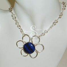 This piece has now been Sold. Do get in touch for Commissions and bespoke orders - Lapis Lazuli Wire Flower Pendant, Part of our series of Flower jewellery this is a single flower pendant necklace hand-crafted in silver plated copper wire by Shalini Austin.