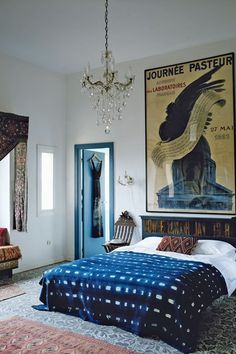 A 1920s French poster hangs above the bed in the main bedroom of Maryam Montague and Chris Redecke's home in the countryside of Marrakesh. Maryam was responsible for much of the interior, weaving in layers of furniture, fabric, pattern and curios - including jewellery and tribal masks - gathered on countless travel trips.