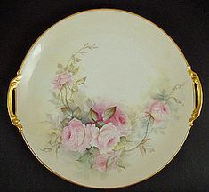 Thus procelain serving platter was produced in France by Coiffe Limoges in the late 19th century. The ground cover has a slightly creamy hue. The flowering pink roses and foliage tumble down the middle of the platter. They are realistically hand painted in shades of pink and green. The rim and handles are trimmed wgold.