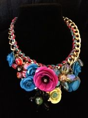 Bold choker style necklace with multi colored metal and resin crystal flowers.
