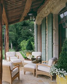 covered terrace out French doors. Low shrub hedge to water oak tree.  pretty furniture. you can see Dollywood just beyond, covered in climbing hydrangea. Low hedges on right lead to Oak and firepit~