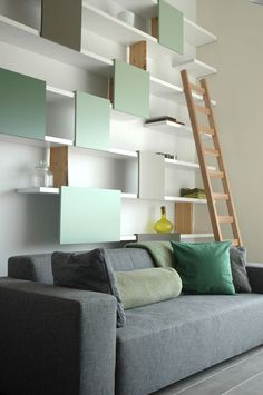 i like this storage idea for an entire wall.  it can be stopped and started to accommodate a bed, possible other things on the wall, etc.  modern, but a bit funky as well.  this is different than most wall shelving i've seen around.  suggestion: put the colored panels on sliders to be able to move them around for possible accessibility to different items.