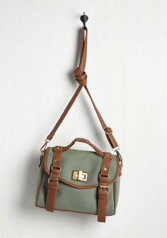 With this canvas bag in tow and your curiosity at its peak, you become a pupil of nature. Perfect for toting your binoculars, flower book, and beyond, this sage green satchel is accented with light brown, vegan faux-leather straps and brushed gold hardware - the visual match to your interest in the outdoors!