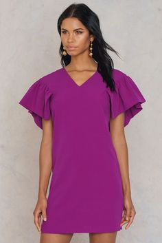 Get frilly with it! The Wide Frill Sleeve Dress by Trendyol comes in the color fuchsia and features a v-neck, frilled sleeves, a mini length, and smooth woven material. Style this piece with black open-toed heels and black tassel earrings!