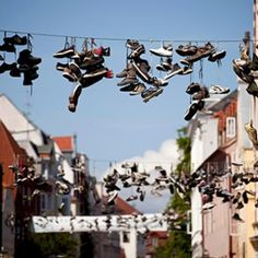 The Norderstraße, Flensburg, Germany There's something eerie about walking down a street as shoes dangle above you. Yet the experience has become so common in this northern German town (four miles from the Danish border) that there's a term for it: shoe graffiti, or simply shoefiti. Some consider the start as an art project; there is a theory that says that a boy who becomes an adult has his shoes hanging outside his house; or that it is a sign from drug dealers telling people where to buy…