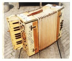 Old small accordion, once it must have been white with blue flowers