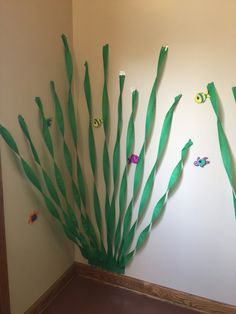 Great way to add depth and color to any area. Use green crepe paper. Attach paper to the base of the wall. Twist paper and cut in varying angles. Add colorful ocean art items to complete the scene. cokesburyvbs.com