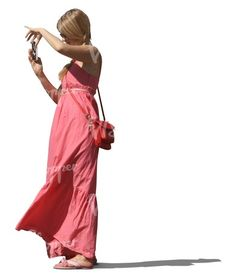 A woman in a pink dress taking a picture