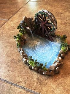 This is a miniature pond with a waterfall attached. The base is made with clay while the surroundings are made with rocks and moss and the water is designed with hot glue. (7.5 X 7.5) for any custom variations please contact me. Shown above is a custom pond completed for a customer