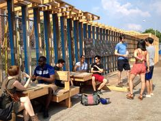 enjoying the seats and tables / interactive community wall transforms fence by chat travieso