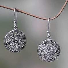Swirling vines and blossoms cover radiant sterling silver disks in this earring design. From Bali's Wayan Asmana, the handcrafted silver earrings evoke the tropical moon.