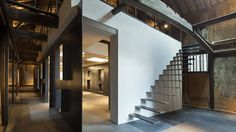Japanese studio yHa Architects has inserted a steel cuboid, wall and stairs inside this former rice mill in Saga Prefecture to create a sake tasting and exhibition space.