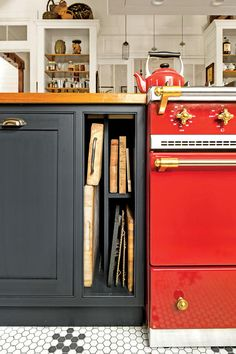 A cherry red Lacanche range anchors the island and is surrounded by navy cabinetry. Built-in nooks keep cutting boards handy.