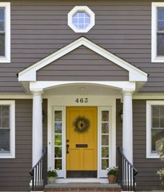 grey wood house with a yellow door