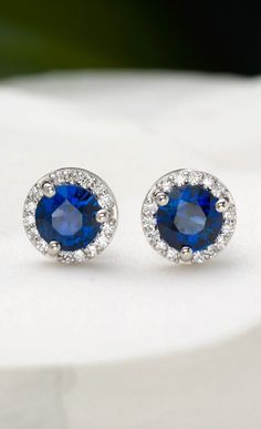 These mesmerizing earrings feature richly hued deep blue sapphire centers surrounded by a stunning halo of pave-set diamonds.