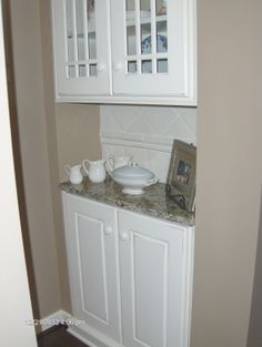 what used to be a shallow pantry at top of stairs, now upper cabinet with glass doors and lower cabinet with granite countertop space