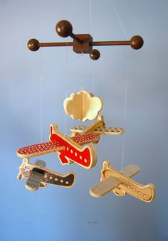 Airplane Mobile: Flying Trees' Airplane Mobile ($90) is made of solid wood and includes four airplanes with a fluffy cloud between them. Each bright airplanes has wings that have been decoupaged with a colorful swatch of designer paper or fabric.