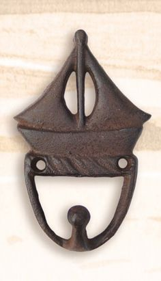 """Cast Iron Sailboat Utility Hook. Handy as can be onboard the boat, in the shop: anywhere indoors, or out. Cast iron antique dark brownish finish.Nautical by nature. Vintage Rustic Cast Iron Hooks. Measurements: 4.75"""" tall x 3"""" wideand hook is 1"""" out from wall. Weight: 6 oz. Coastal or Beach House Wall Hooks:their stylish maritime design are also used for coat & towel hooks, pool hooks especially nice in bathrooms and aquatic themed spaces."""