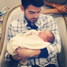 Aw look, it's my first celebrity crush, holding a baby...and...still looking like fire...admitting it.