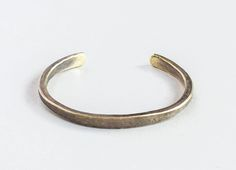 * Hand-forged, contoured silhouette with a slimmer flat face and       tapered edges      * Available in a work patina or high-polish finish  We offer each piece in solid American brass, sterling silver or pure  copper. This cuff is left uncoated and will evolve with wear.Before  leaving our shop, each item is stamped with our Studebaker maker's mark and  its city of origin, Pittsburgh.LEARN MORE