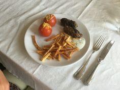 Hoofdgerecht frietjes met kruidige gehaktstaaf met tzatziki en gevulde tomaten.