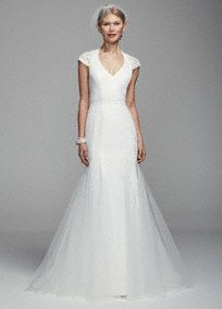 Make a lasting impression on your special day in this ultra-feminine lace trumpet gown!  Scalloped lace cap sleeve trumpet gown with v-neckline features illusion back and godet detailing.  Attached belt at waist.  Sweep train. Sizes 0-14.  Fully lined. Button back closure. Imported polyester. Dry clean only.  To preserve your wedding dreams, try our Wedding Gown Preservation Kit.