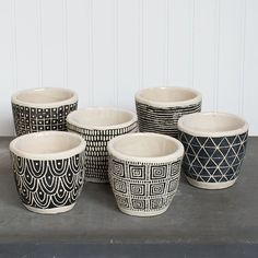 Intricate and distinct geometric motifs, all rendered in black and white, make pint-size artworks of these cement pots. Painted Plant Pots, Ceramic Plant Pots, Cement Pots, Painted Flower Pots, Clay Pots, Paint Flowers, Painted Pebbles, Terracotta Flower Pots, Cement Flower Pots
